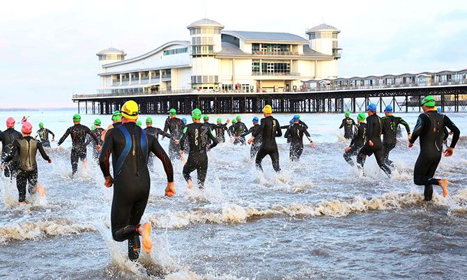 Competitors running in to the water at the start of Titan Weston Middle Distance Triathlon